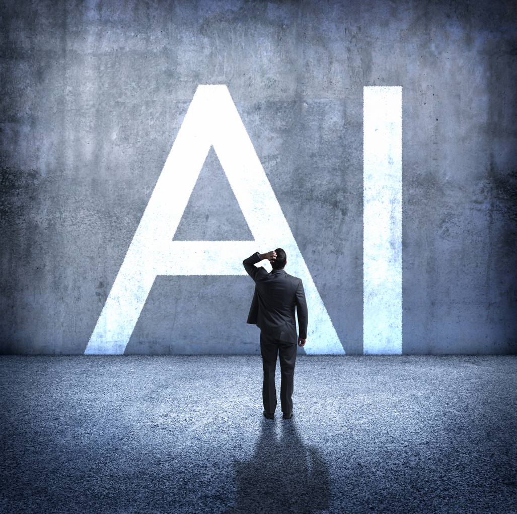 "A rear view of a man standing with his hand on top of his head as he stands below the large letters, ""AI"" which stand for artificial intelligence. He is concerned about the unknown implications of the rollout of artificial intelligence on our society. AI"
