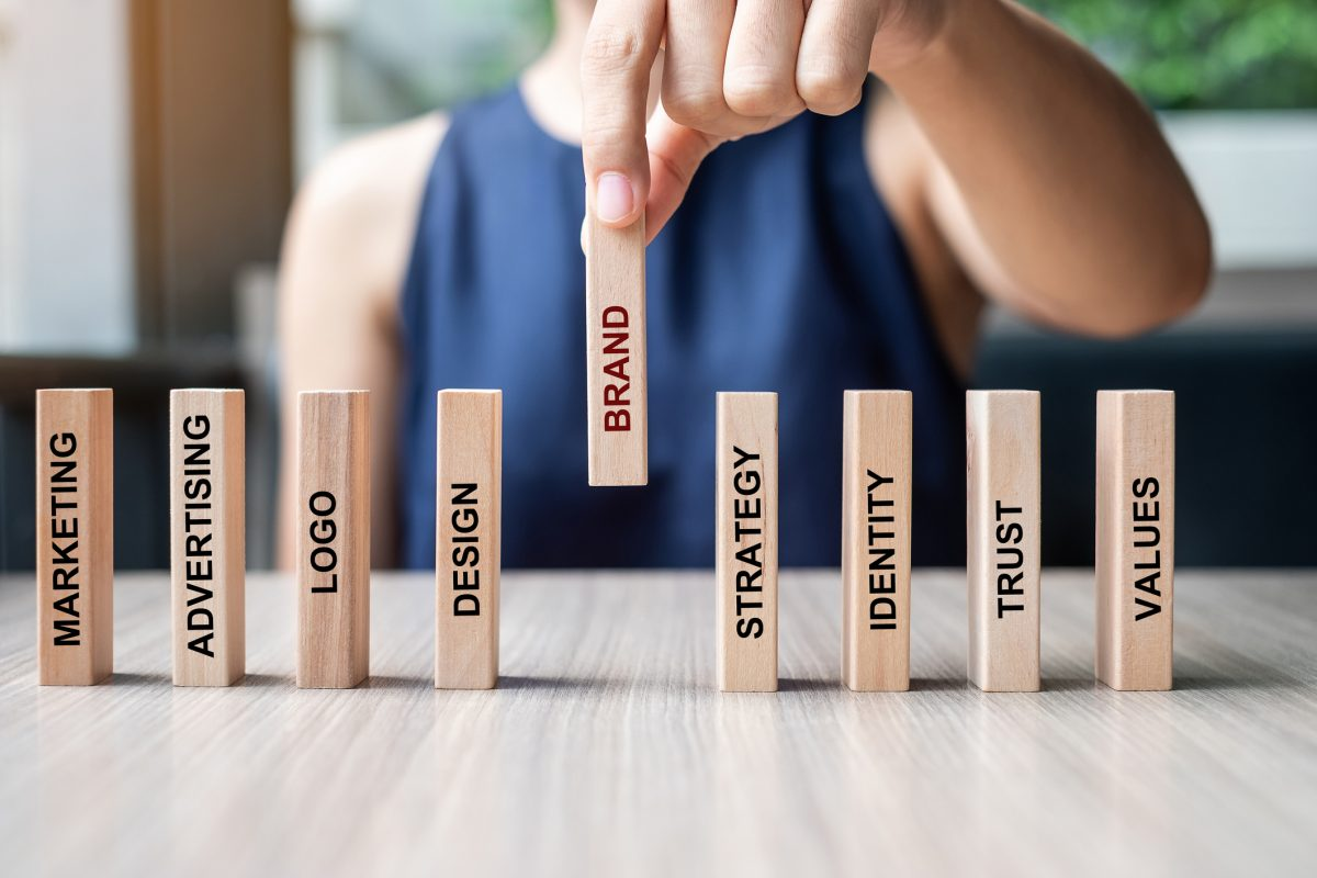 representing marketing tips - Businesswoman hand placing or pulling wooden Dominoes with BRAND text. and Marketing, Advertising, Logo, Design, Strategy, Identity, Trust and Values. Product development concept