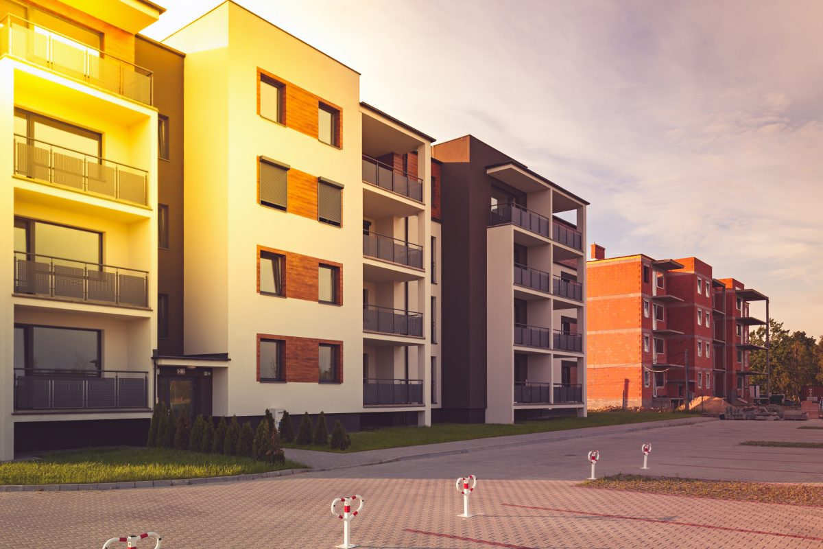 New multi family home buyer block with balconies, bright facade and wooden panels.
