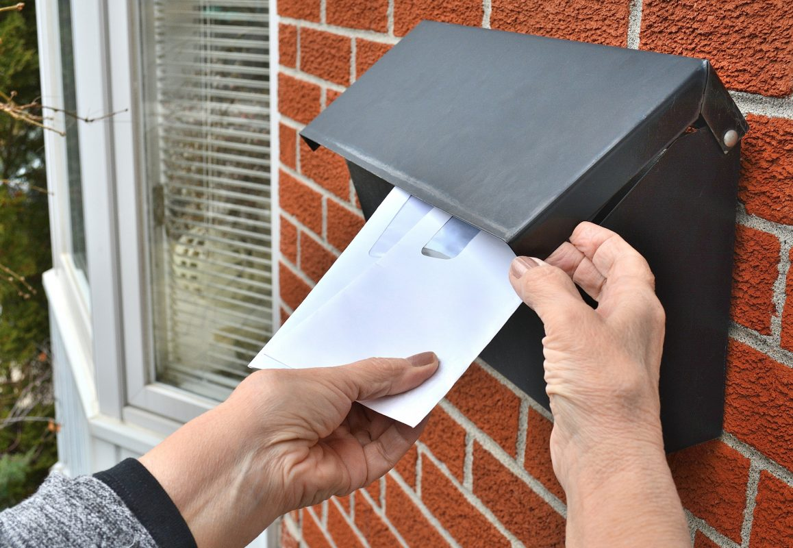 direct mail marketing - Lifestyle...This is a close up shot of a home owner, taking several envelopes from a front door, residential, letterbox.