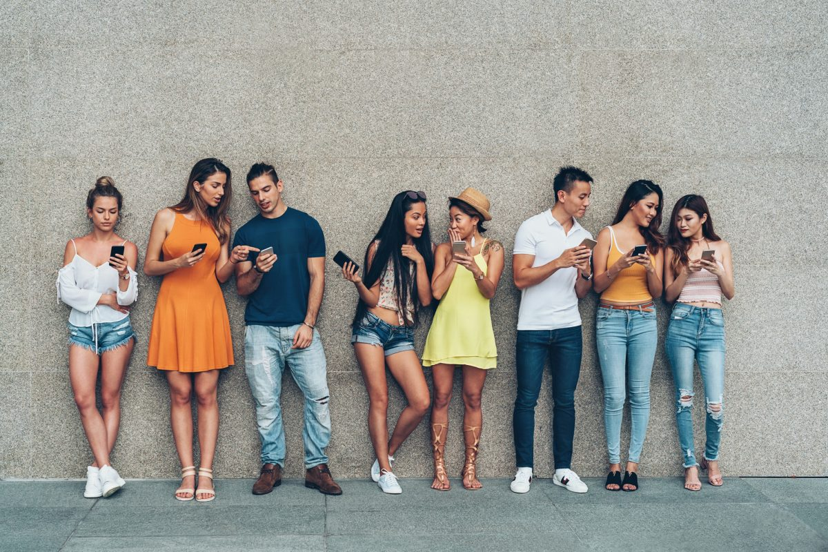 Group of young people with smart phones standing in a row outdoors against a wall, representing how to market to millennials