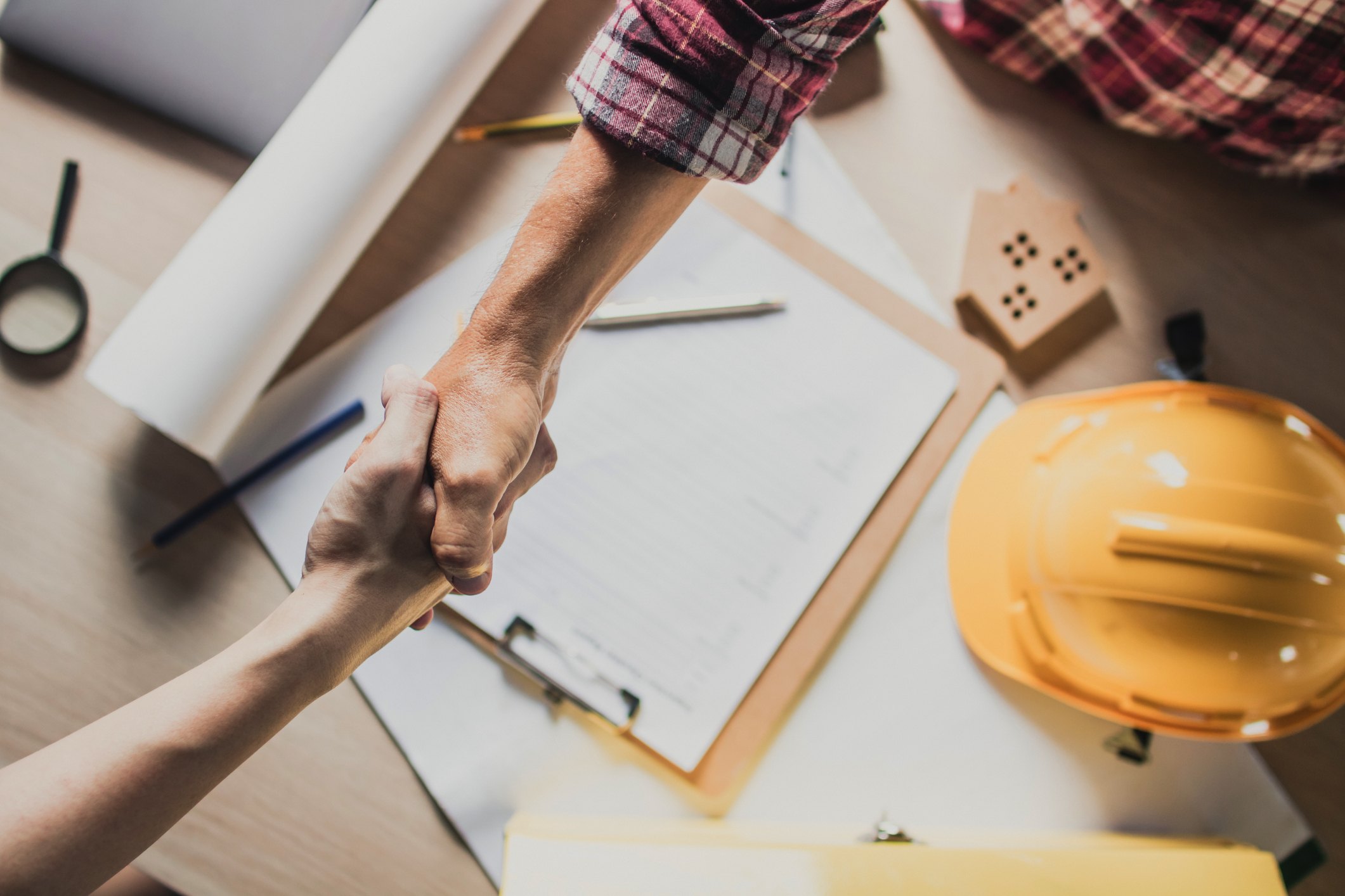 top view hand shake of engineer and building contractor on table, representing Home Builder SEO and home builder marketing and home builder keywords